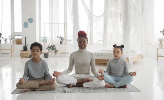 personal development depicted by woman and two children in meditative pose